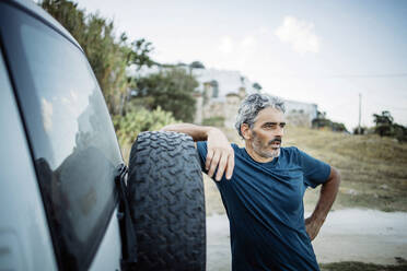 Mature man standing at his off-road vehicle - OCMF00644