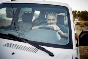 Smiling mature man sitting in his off-road vehicle - OCMF00647
