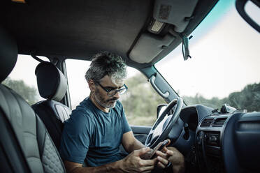 Mature man sitting sitting in his off-road vehicle checking his smartphone - OCMF00650