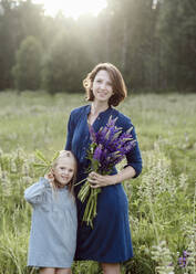 Portrait of mother and little daughter with bunch of lupines on a meadow - EYAF00473