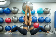 Twin sisters in gym practicing with a fitness ball - OCMF00657