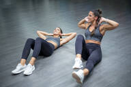 Twin sisters training in gym doing sit-ups - OCMF00660