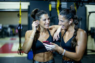 Twin happy sisters in gym with smartphone and headphones - OCMF00669