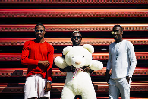 Portrait of three cool young men with huge teddy bear at red wall - OCMF00675