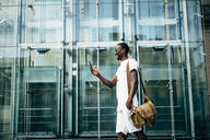 Young man using mobile phone in the city - OCMF00681