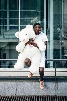 Smiling young man holding huge teddy bear - OCMF00687