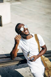 Happy young man with earphones and mobile phone in the city - OCMF00690