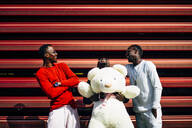Three laughing young men with huge teddy bear at red wall - OCMF00696