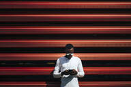 Young man using mobile phone at a red wall - OCMF00702