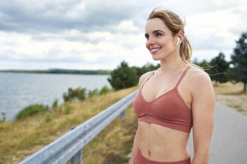 Portrait of smiling sporty woman with wireless earphones at the lakeside - BSZF01389