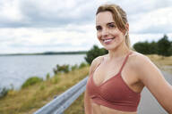 Portrait of smiling sporty woman with wireless earphones at the lakeside - BSZF01392