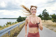 Portrait of smiling athletic woman jogging outdoors - BSZF01395
