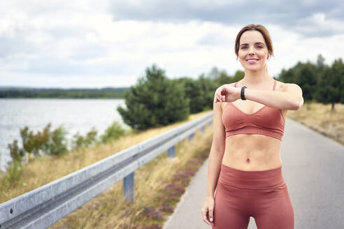 Portrait of fit woman checking smartwatch during outdoor jogging session - BSZF01398