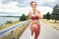 Smilling athletic woman practicing outdoors near lake - BSZF01407