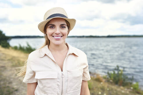 Portrait of smiling woman at the lakeside - BSZF01410