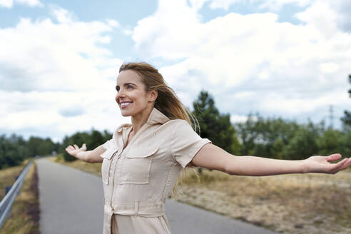 Happy woman standing on a rural road with outstretched arms - BSZF01419