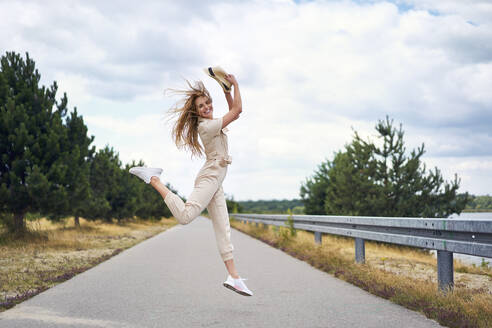 Cheerful woman jumping on rural road - BSZF01425