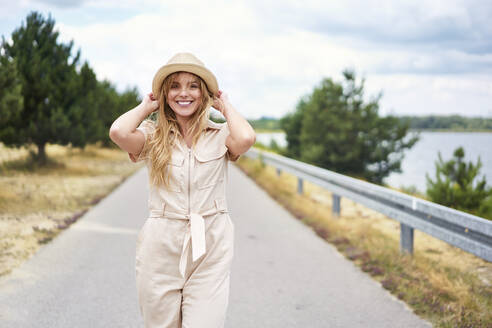 Portrait of smiling woman on rural road at the lakeside - BSZF01428
