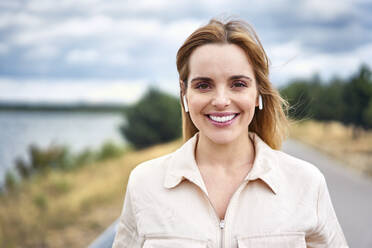 Portrait of smiling woman with wireless earphones in nature - BSZF01437
