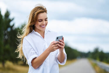 Happy woman checking cell phone on rural road - BSZF01440