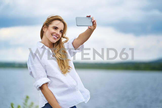 Happy woman taking selfie with smartphone at the lakeside - BSZF01443 - Bartek Szewczyk/Westend61