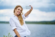Happy woman taking selfie with smartphone at the lakeside - BSZF01443