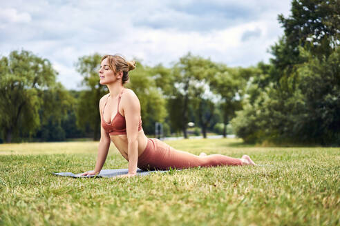Woman doing cobra pose during yoga training in the park - BSZF01449