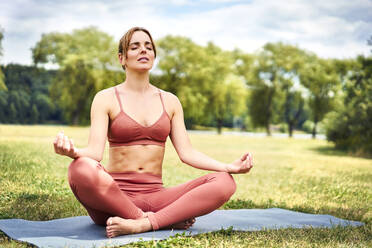 Woman practicing yoga in park meditating - BSZF01455