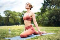 Woman practicing yoga in park - BSZF01458