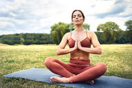 Woman practicing yoga in park meditating - BSZF01464