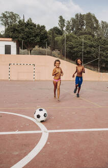 Two children playing soccer on a soccer field - LJF00982