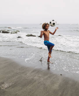 Boy playing with a football on the beach - LJF00988