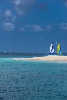 Catamarans moored at white sand beach against blue sky on Palm island, Grenadines islands, St. Vincent and the Grenadines, Caribbean - RUNF03087