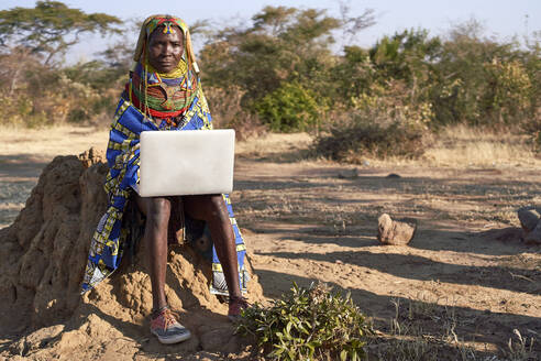 Traditional Muhila woman, wearing sneakers,neakers working on her laptop, Kehamba, Chibia, Angola - VEGF00629