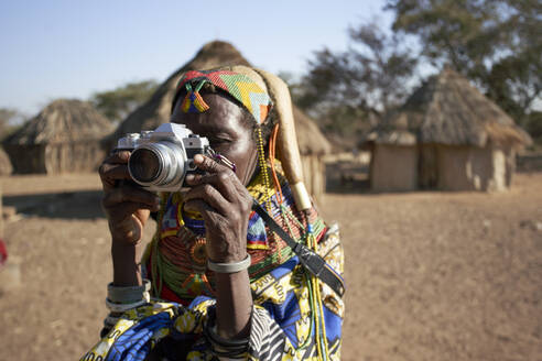 Muhila traditional woman taking pictures with a camera, Kehamba, Chibia, Angola - VEGF00635