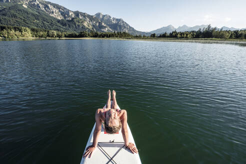 Smiling girl on a stand up paddle board, Bannwaldsee, Allgaeu, Bavaria, Germany - WFF00087