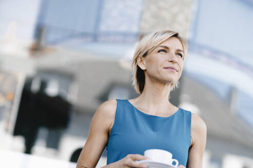 Businesswoman holding cup of coffee, portrait - KNSF06310