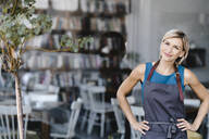 Portrait of blond woman, standing in front of her own coffee shop - KNSF06322