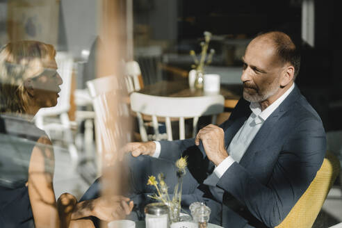Businessman and woman having a meeting in a coffee shop - KNSF06367