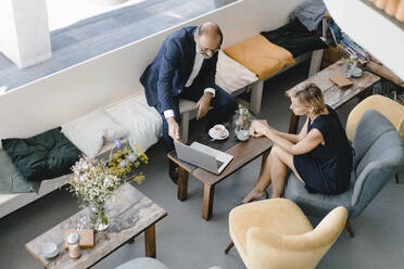 Businessman and woman having a meeting in a coffee shop, discussing work - KNSF06415