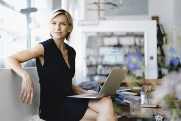 Businesswoman sitting in coffee shop, using laptop - KNSF06421
