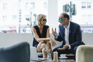 Businessman and woman wearing super hero masks, having a meeting - KNSF06427