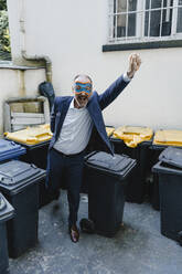 Businessman with super hero mask, fighting waste - KNSF06430
