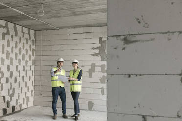 Two architects talking about architectural plan while standing at construction site - AHSF00805