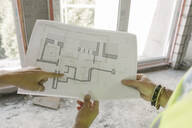 Two architects pointing a architectural plan at construction site - AHSF00808