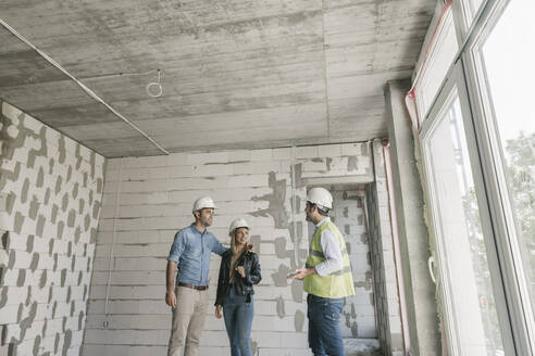 Lithuania, Vilnius, Architect talking with future owners on construction site - AHSF00817