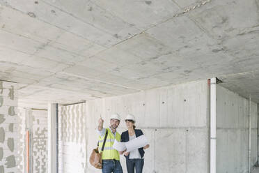 Male architect and female manager talking about architectural plan at construction site - AHSF00823