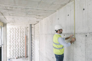 Architect metering a wall at construction site - AHSF00826