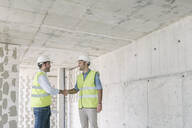 Two workers shaking hands construction site - AHSF00832