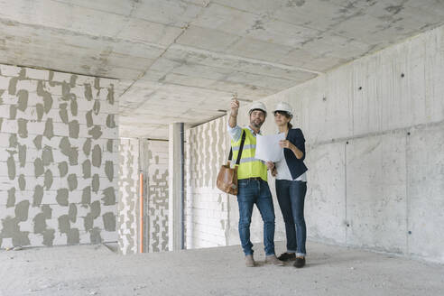 Male architect and female manager talking at construction site - AHSF00844